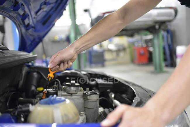 Car mechanic checking motor oil — Stock Photo