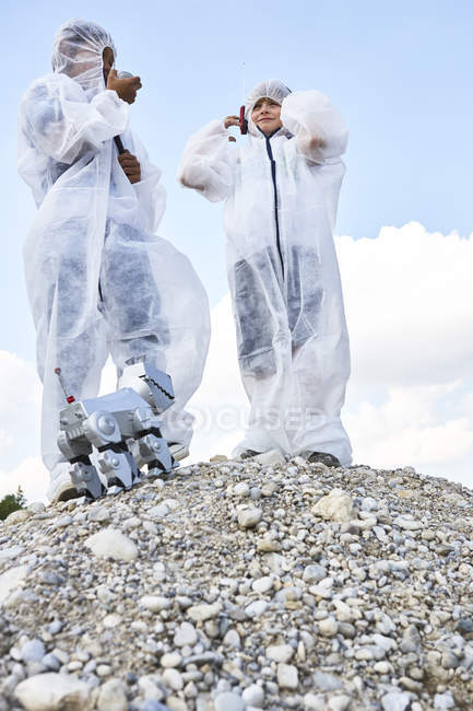 Two boys with robot on hill — Stock Photo