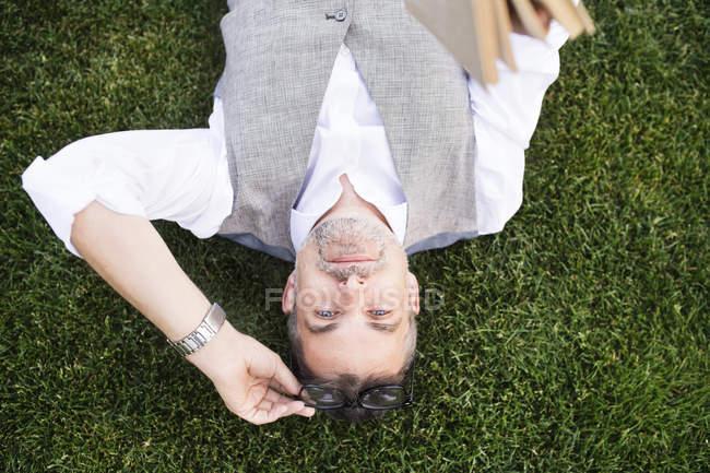 Бізнесмен, що лежить на траві — стокове фото