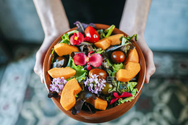 Hands holding bowl of mixed salad — Stock Photo