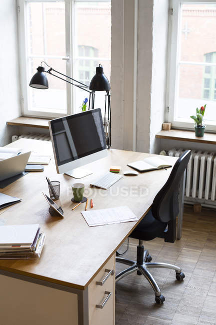 Desk with documents and computer screen — Stock Photo