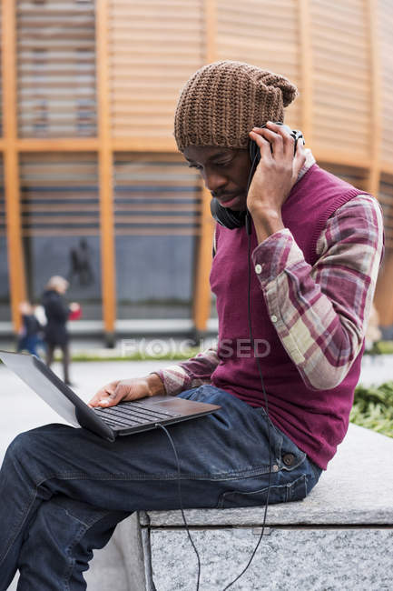 Homme avec casque à l'aide d'un ordinateur portable — Photo de stock