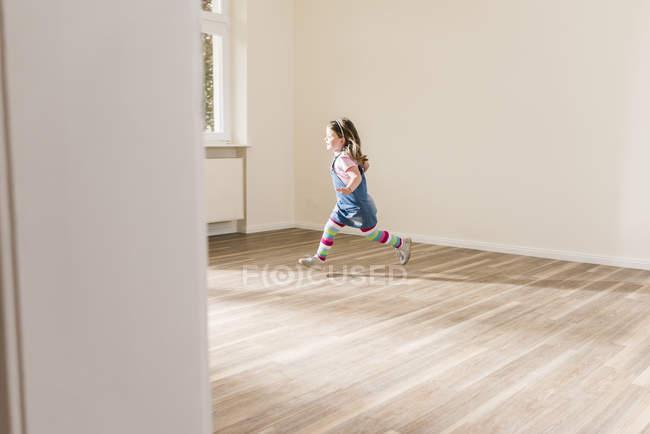 Happy girl courir dans un appartement vide — Photo de stock