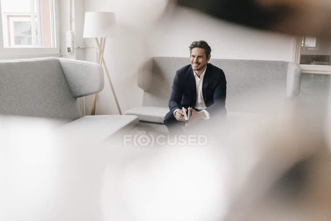 Businessman sitting on couch — Stock Photo