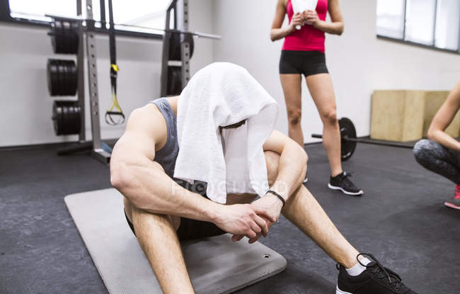 Exhausted athlete with towel on head — Stock Photo