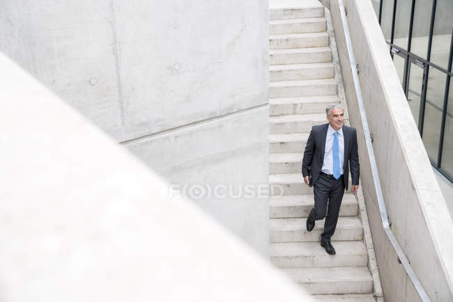 Busiinessman walking downstairs — Stock Photo