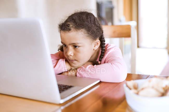 Menina olhando para laptop na mesa — Fotografia de Stock