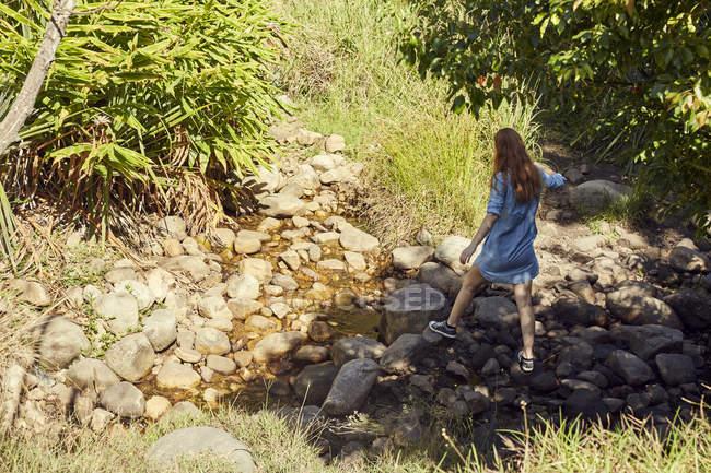 Donna che cammina vicino ruscello di montagna — Foto stock