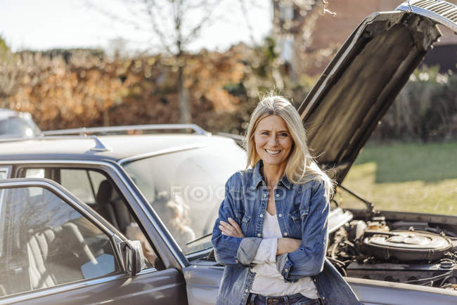 Woman standing next to vintage car — Stock Photo