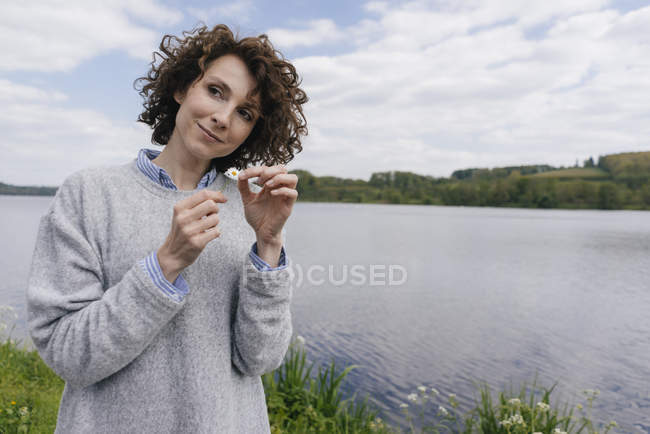 Woman plucking daisy petals — Stock Photo