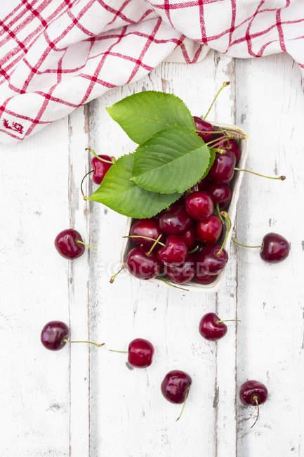Cardboard box of fresh cherries — Stock Photo