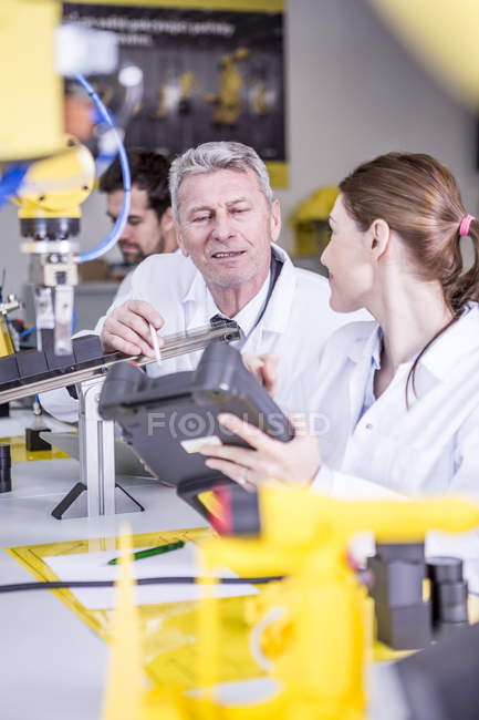 Two engineers in factory talking about device — Stock Photo
