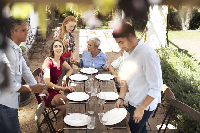 Family setting table for lunch outside — Stock Photo