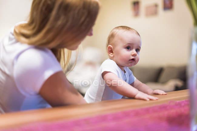 Mère et bébé fils assis à table — Photo de stock