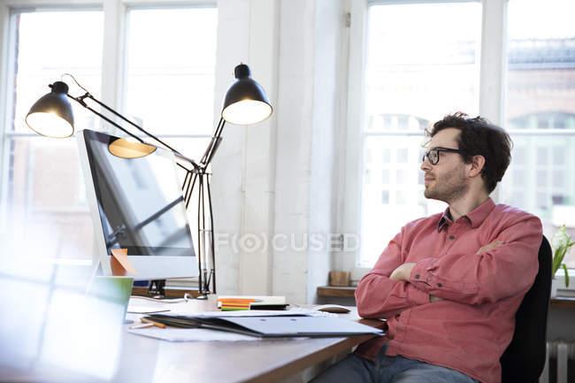 Mann sitzt am Schreibtisch im Büro — Stockfoto