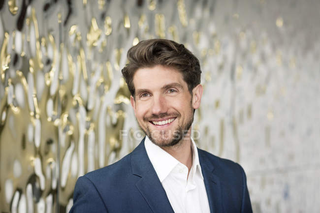 Portrait of attractive smiling businessman in a foyer — Stock Photo
