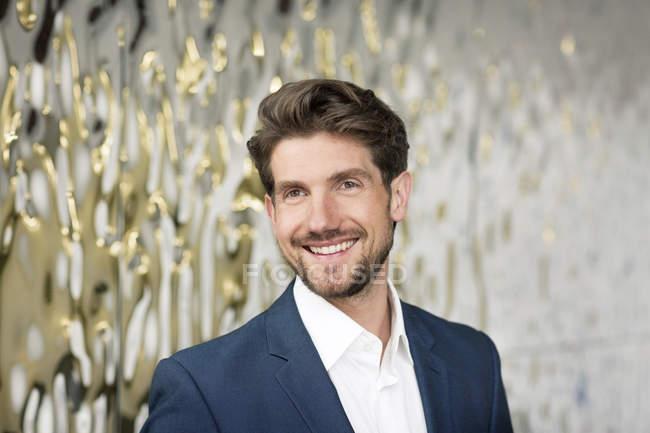 Porträt eines attraktiven lächelnden Geschäftsmannes im Foyer — Stockfoto