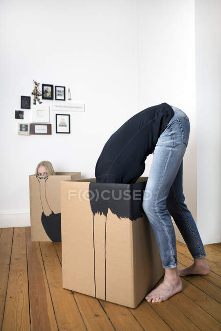 Girl and adult inside cardboard boxes — Stock Photo