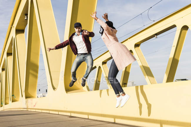 Paar springt auf Brücke — Stockfoto