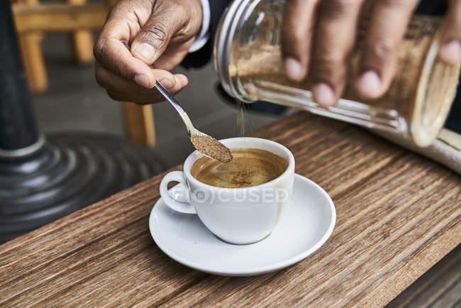 Macho mãos derramar açúcar no café — Fotografia de Stock