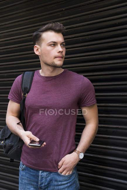 Hombre con teléfono celular cerca de persiana enrollable - foto de stock