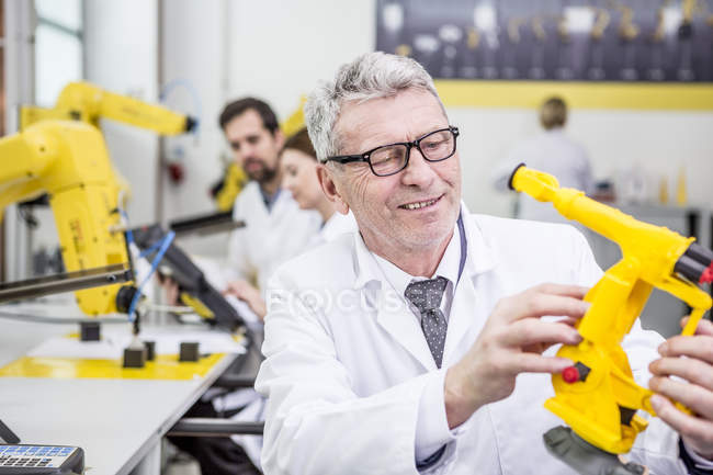 Engineer holding model of an industrial robot — Stock Photo