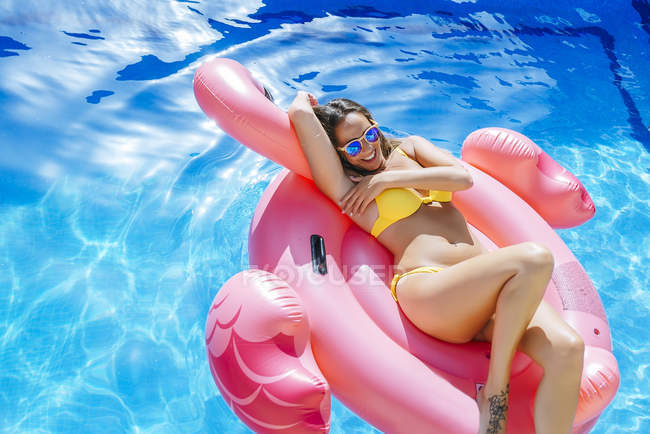 Young woman on pink flamingo float — Stock Photo