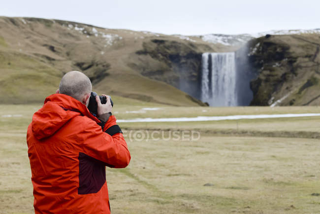 Photographer making picture at Skogafoss waterfall — Stock Photo