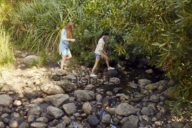 Donne attraversano ruscello di montagna — Foto stock