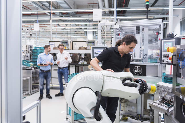 Man operating assembly robot — Stock Photo