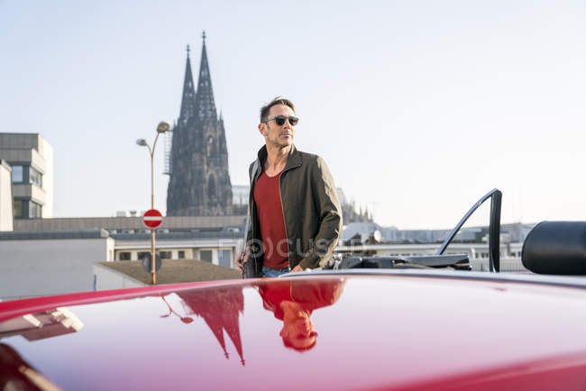 Man walking next to sports car — Stock Photo