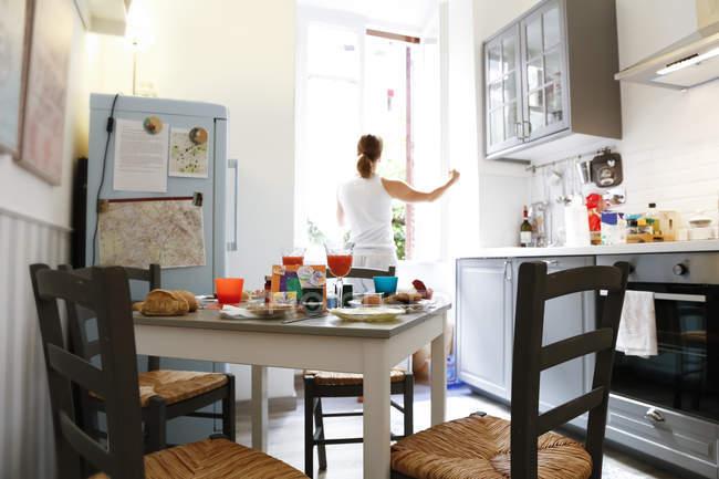 Жінка, відкривши вікно кухні — стокове фото