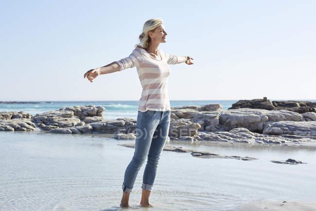 Woman standing at sea beach — Stock Photo