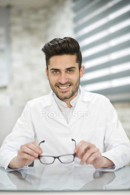 Optician sitting in shop — Stock Photo