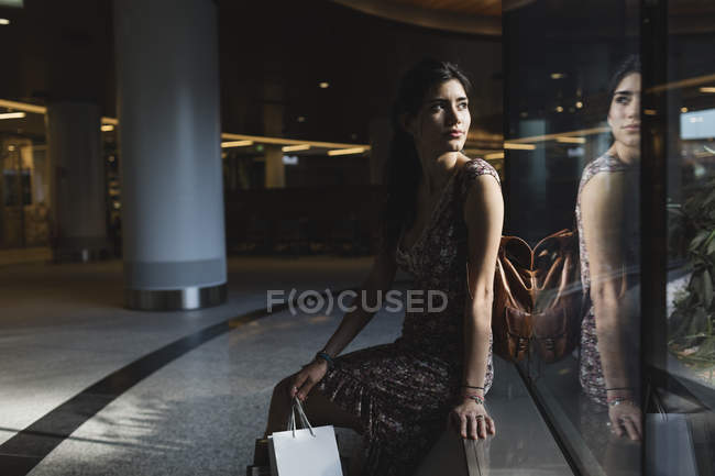 Woman sitting with shopping bag — Stock Photo