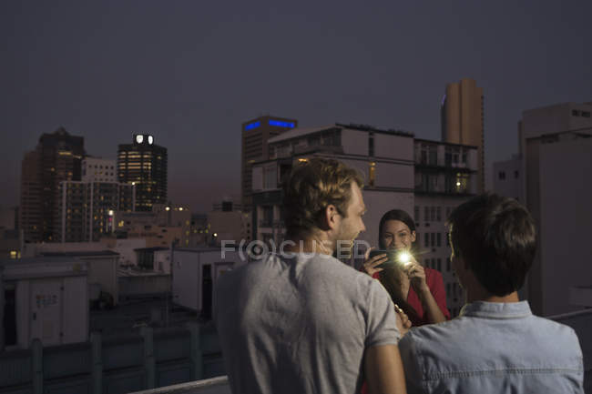 Woman taking pictures at rooftop party — Stock Photo