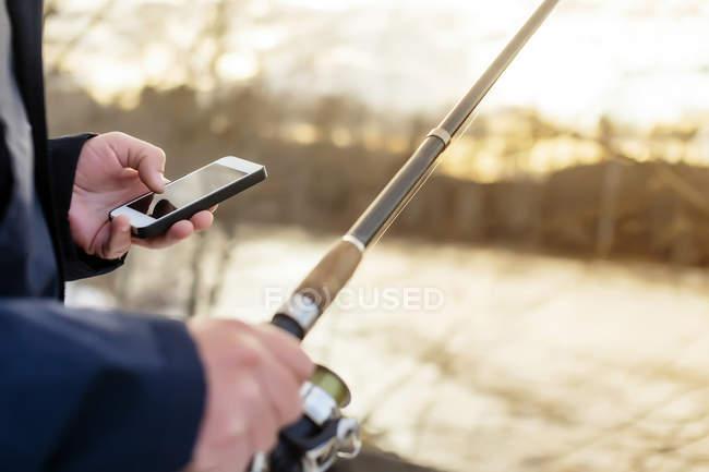 Homem olhando para o celular de pesca — Fotografia de Stock