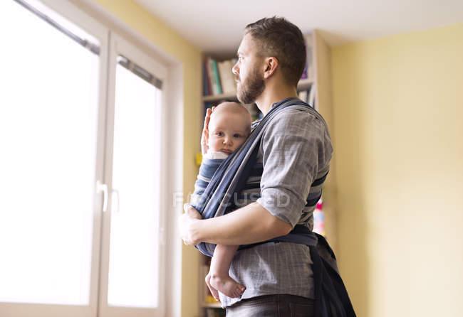 Батько з сином дитина дивиться з вікна — стокове фото