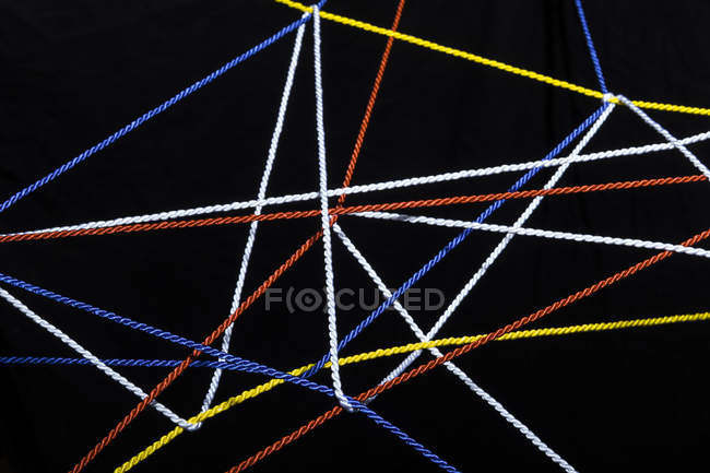 Connected threads in front of black background — Stock Photo