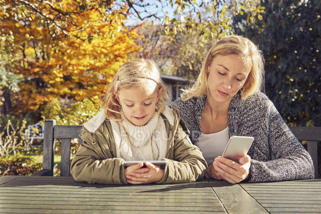 Mother with daughter using gadgets — Stock Photo