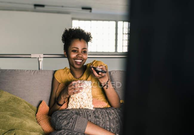 Jeune femme assise sur le canapé et regarder la télévision en riant — Photo de stock