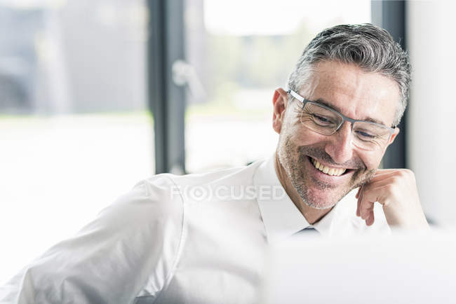Businessman with stubble sitting in office — Stock Photo