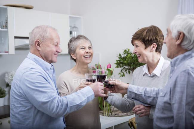 Seniorenpaare stoßen mit Rotwein an — Stockfoto