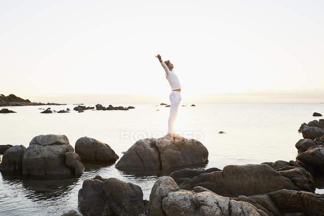 Man doing yoga exercise on a rock — Stock Photo