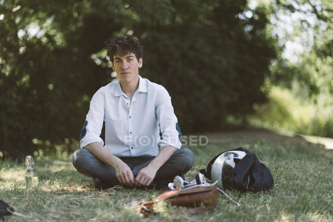 Portrait of young man sitting on meadow in park — Stock Photo