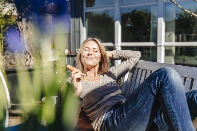 Женщина отдыхает на скамейке в саду — стоковое фото