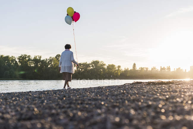 Senior woman with balloons strolling — Stock Photo