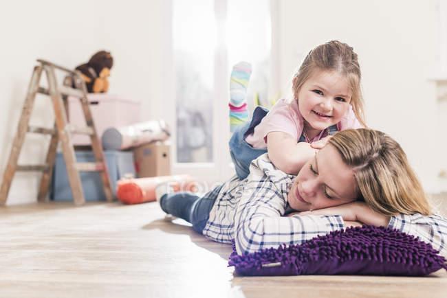 Madre e figlia che si abbracciano sul pavimento — Foto stock