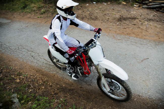 Motocross biker riding in forest — Stock Photo