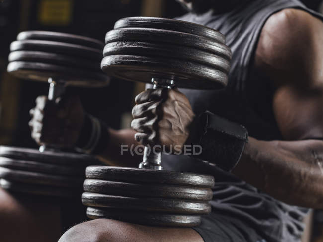 Athlete traing with dumbbells — Stock Photo